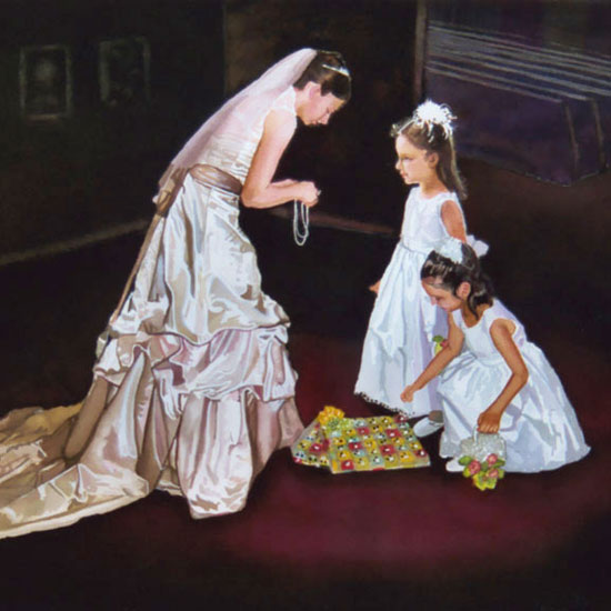 2 five-year-old girls dressed in white gowns being given necklaces by a woman in a wedding dress